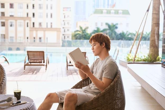 Jovem asiático lendo um livro à beira da piscina em um dia ensolarado de verão