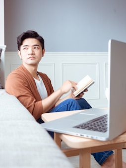 Jovem asiático lendo um livro enquanto relaxa em casa