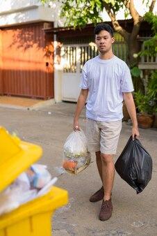 Jovem asiático levando o lixo para fora de casa