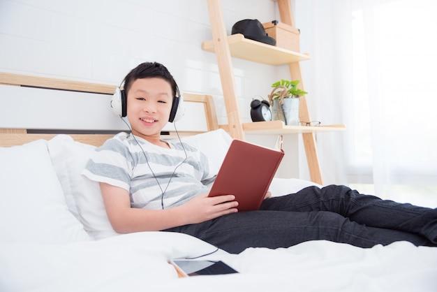 Jovem, asiático, menino, desgastar, headset, escutar, música