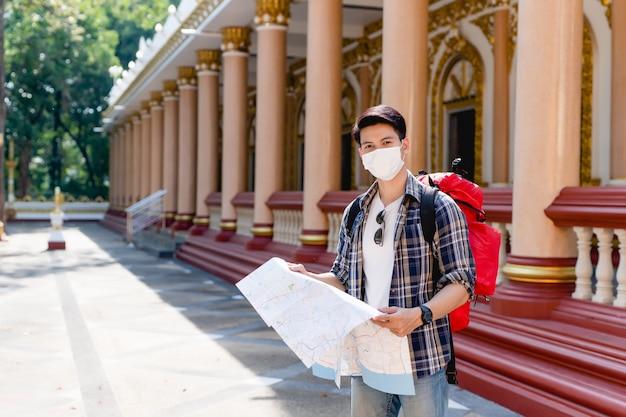 Jovem asiático mochileiro masculino com máscara facial em pé e verificando a direção no mapa de papel na mão no belo templo tailandês.