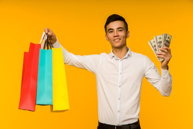 Jovem asiático mostrando sua sacola de compras e dinheiro