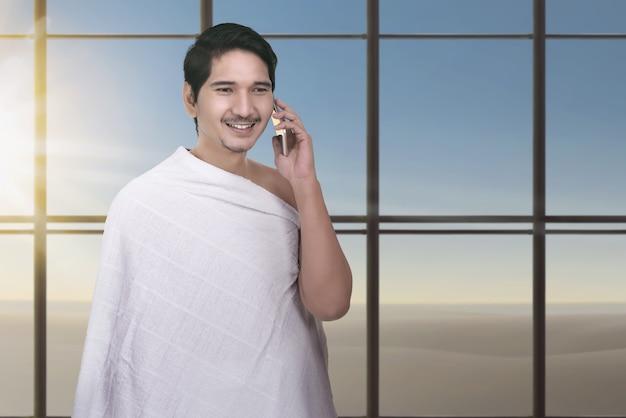 Jovem, asiático, muçulmano, homem, com, ihram, pano, usando, cellphone