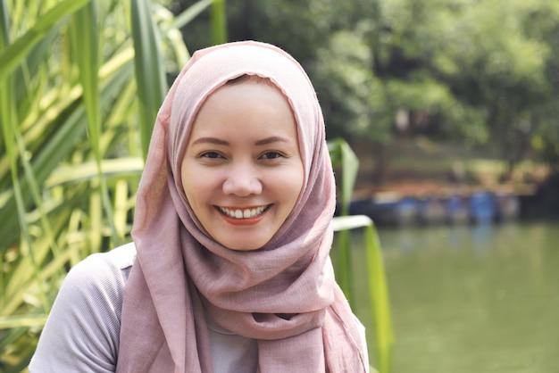 Jovem, asiático, muçulmano, mulher, em, hijab, com, smiley enfrentam