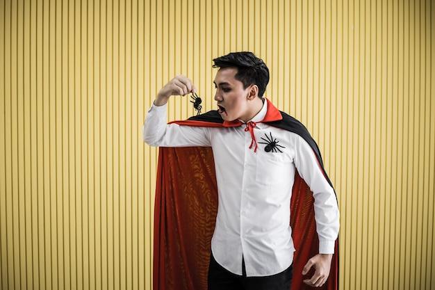 Jovem asiático no traje de drácula e comer a aranha preta sobre fundo amarelo do conceito de halloween. retrato de homem adolescente vestido de drácula para comemorar o festival de halloween.