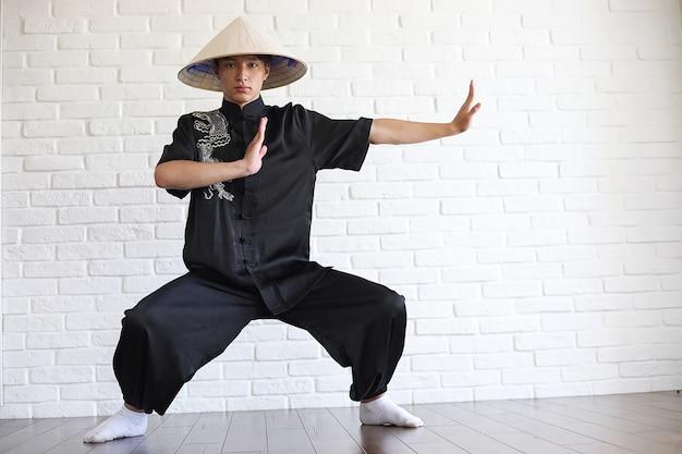 Jovem asiático novato em um fundo de parede de tijolo branco