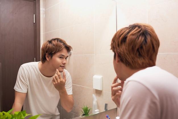 Jovem asiático olhando no espelho e verificando sua pele no banheiro