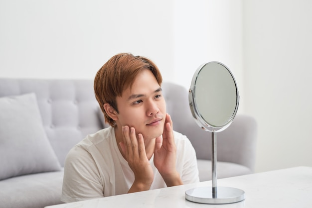Jovem asiático olhando no espelho e verificando sua pele