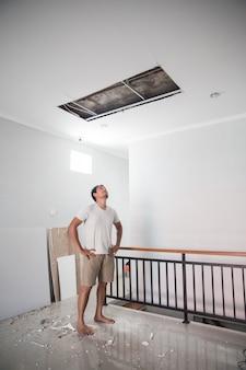 Jovem asiático olhando para o teto quebrado de sua casa