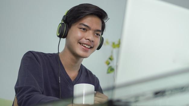 Jovem asiático online usando seu laptop com um copo de bebida