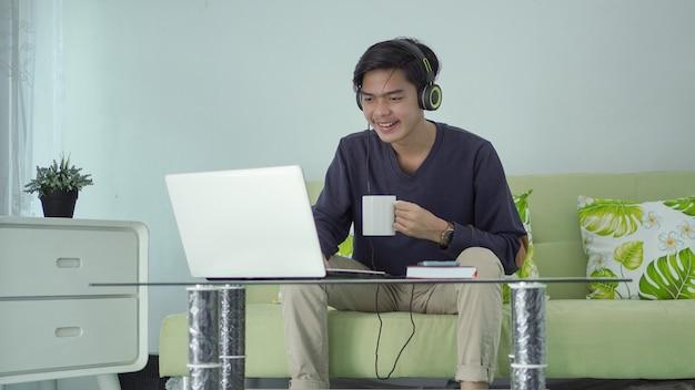 Jovem asiático ouvindo som em seu laptop com um copo de bebida em casa