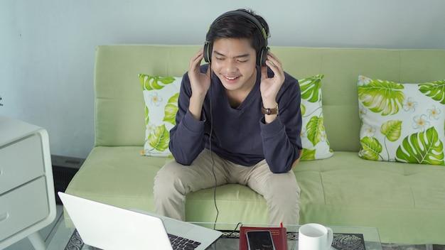 Jovem asiático ouvindo usando fone de ouvido do celular, acompanhado de um copo de bebida em casa