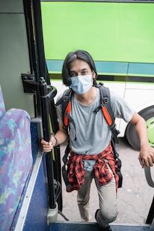 Jovem asiático para cima usando máscara facial e mochila prestes a pegar o ônibus na estação rodoviária. conceito covid-19