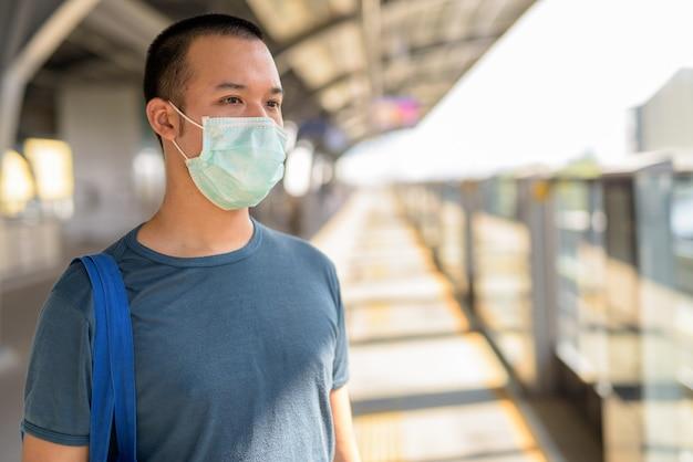 Jovem asiático pensando com máscara para proteção contra surto de coronavírus na estação de trem do céu
