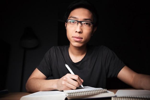 Jovem asiático pensativo de óculos, estudando e escrevendo à mesa no quarto escuro