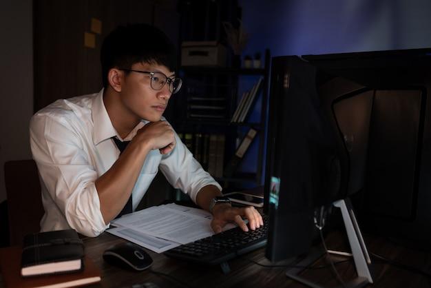 Jovem asiático pensativo trabalhando até tarde, concentrado e sério