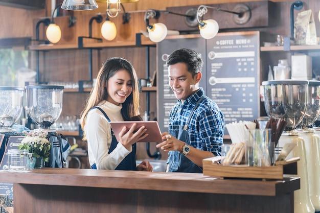 Jovem asiático pequeno empresário conversando com colegas e usando tecnologia de tablet