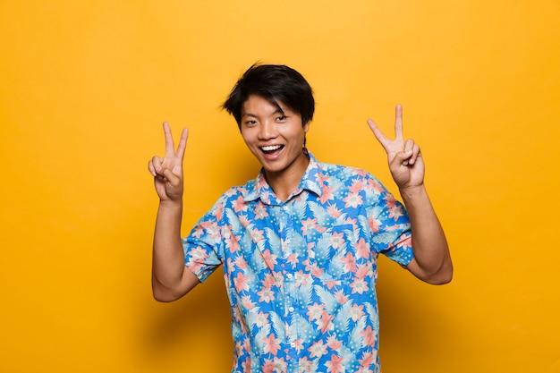 Jovem asiático posando isolado sobre o espaço amarelo, mostrando um gesto de paz.