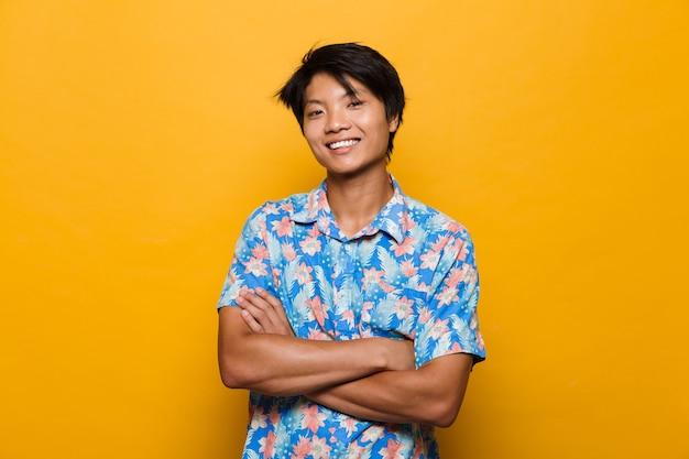Jovem asiático posando isolado sobre o espaço amarelo.