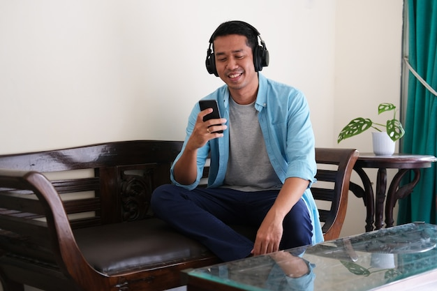 Jovem asiático relaxando dentro de sua casa enquanto ouve música