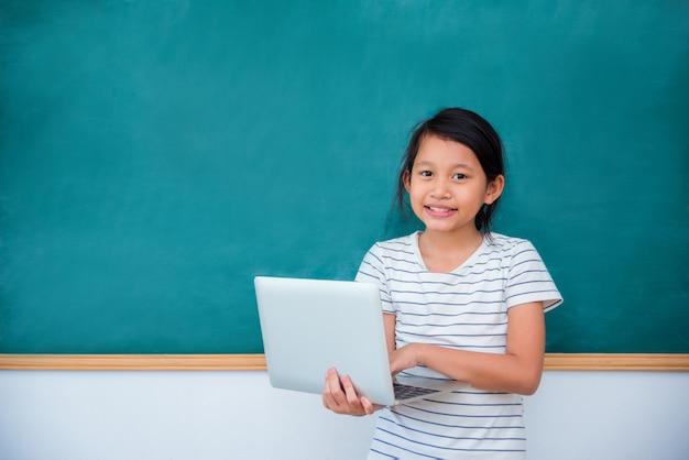 Jovem, asiático, schoolgirl, segurando, laptop, computador, sorrisos, frente, chalkboard