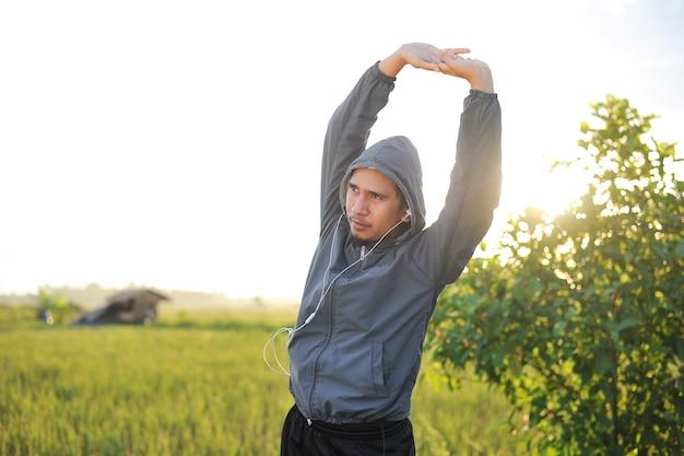 Jovem asiático se aquece antes de correr no arrozal ao pôr do sol, ao mesmo tempo em que ouve música no fone de ouvido