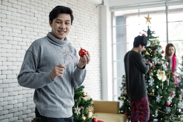 Jovem asiático segura o brinquedo para decorar a árvore de natal com um sorriso no qual tem um plano de fundo de amigos. comemoração do ano novo em casa. feliz natal e boas festas.