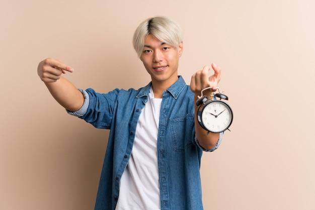 Jovem asiático segurando despertador vintage