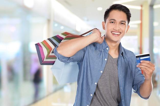 Jovem, asiático, segurando sacolas, cartão crédito, cima