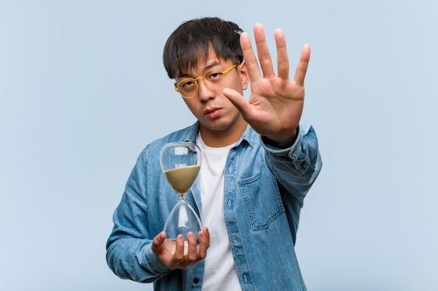 Jovem asiático, segurando um relógio de areia, colocando a mão na frente