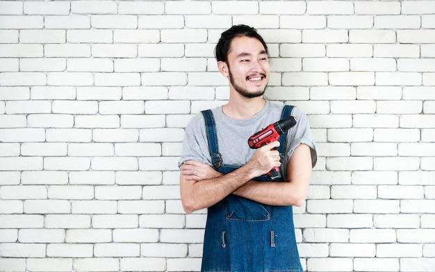 Jovem asiático segurando uma furadeira em frente a uma parede de tijolos brancos, sorrindo e olhando para a câmera, conceito para casa faça você mesmo