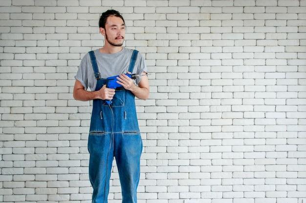 Jovem asiático segurando uma furadeira em frente a uma parede de tijolos brancos, sorrindo e olhando para fora, conceito para casa faça você mesmo