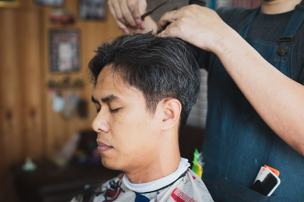 Jovem asiático sendo cortado de cabelo com tesoura por barbeiro profissional na barbearia. cabeleireiro usando pente e tesoura para cortar o cabelo.