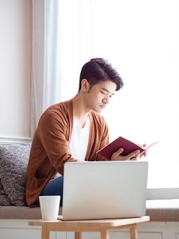 Jovem asiático sentado à mesa em frente ao computador portátil