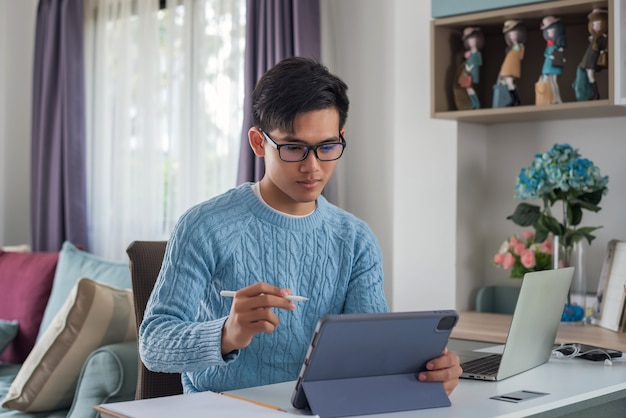 Jovem asiático sentado em casa trabalhando em um tablet