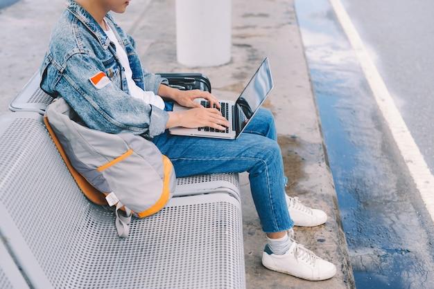 Jovem asiático sentado na cadeira no ponto de ônibus do aeroporto e usando um laptop
