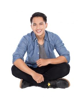 Jovem asiático sentado no chão, sorrindo