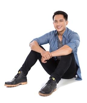 Jovem asiático sentado no chão, sorrir
