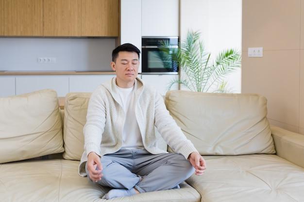 Jovem asiático sentado no sofá em posição de lótus e meditando na calça