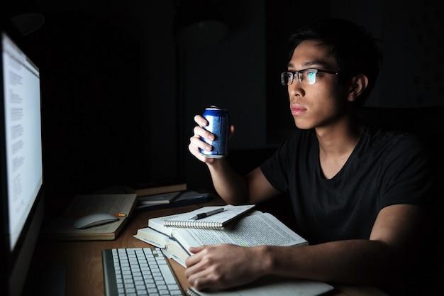 Jovem asiático sério estudando com o computador e bebendo refrigerante no quarto escuro