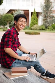 Jovem asiático sorridente com camisa xadrez sentado e usando o laptop ao ar livre