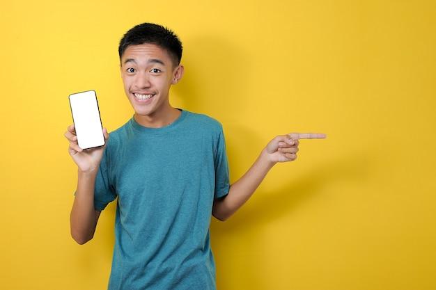 Jovem asiático sorridente feliz mostrando o telefone celular com a outra mão apontando para o espaço vazio no fundo colorido amarelo