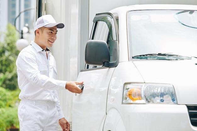 Jovem asiático sorridente jovem entregador de terno branco e boné abrindo a porta da van