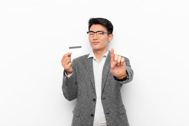 Jovem asiático sorrindo com orgulho e confiança, fazendo a pose número um triunfante, sentindo-se como um líder