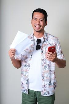 Jovem asiático sorrindo feliz enquanto segura a passagem aérea e o telefone celular