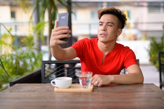 Jovem asiático tirando uma selfie em uma cafeteria ao ar livre