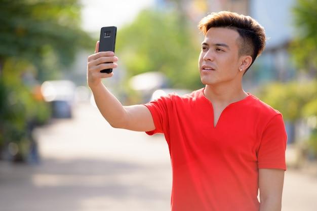 Jovem asiático tirando uma selfie na rua ao ar livre