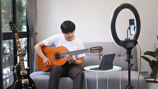 Jovem asiático tocando violão e streaming de vlog online em casa.