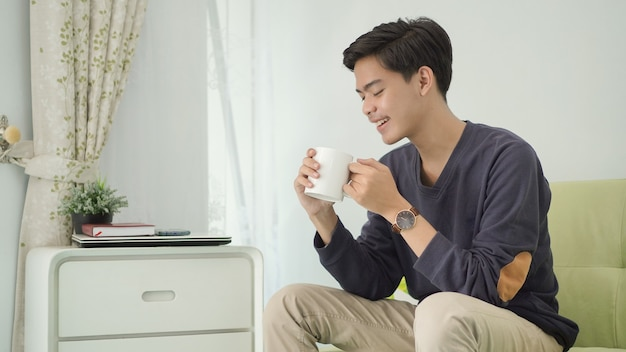 Jovem asiático tomando uma bebida em casa depois do trabalho