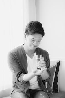 Jovem asiático tomando vitamina dentro de casa
